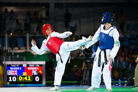 SIDE KICK: Samantha Kassman (in red) launching an attack on Bianca Walkden in their +67kg competition in women's Taekwondo. PHOTO: J. Pini/ Team PNG.